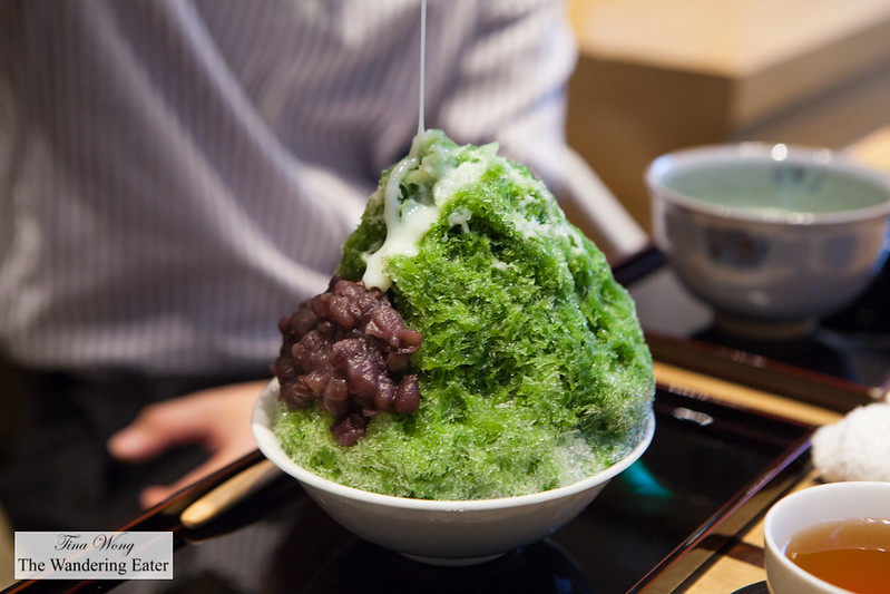 Pouring condensed milk on to the matcha kakigori (かき氷) topped with mochi and adzuki red bean