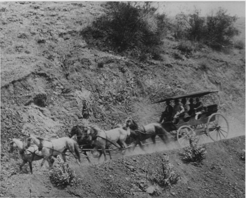 Stage coach and horses on a mountainous dirt road, ca.1900