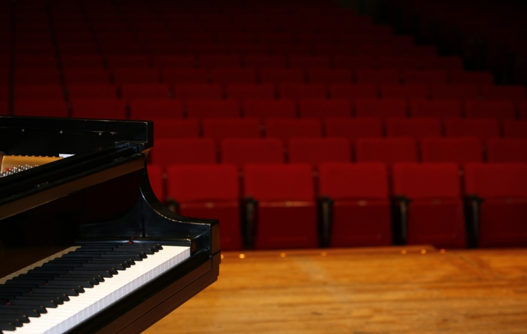 piano on stage of concert hall
