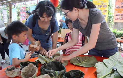 親子檔認真聆聽王馨曼(右一)解說如何運用麵包樹葉製作成碗。(攝影:謝宗璋)