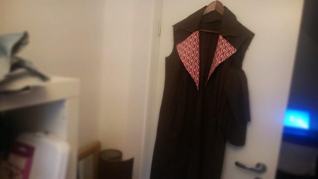 Halbfertiger Mantel in braun mit rotem Reverskragen.