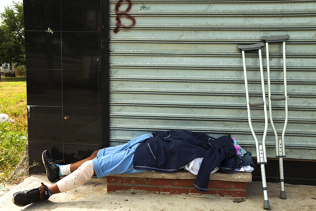 Man sleeping next to crutches on Broadway on 8-27-15--Camden