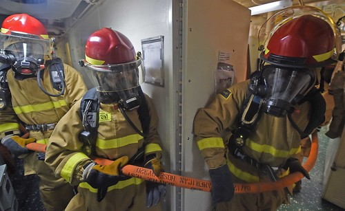 INDIAN OCEAN - Sailors from a repair locker enter a space to combat a simulated fire during a general quarters exercise onboard USS Ashland (LSD 48).