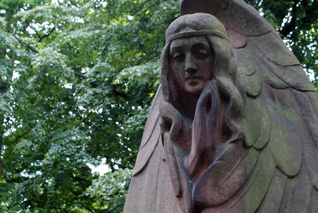 Powazki à Varsovie : Statue représentant le visage d'une femme-ange aux cheveux attachés par un bandeau.