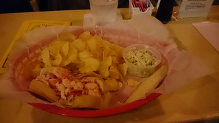 A lobster roll, crisps and coleslaw