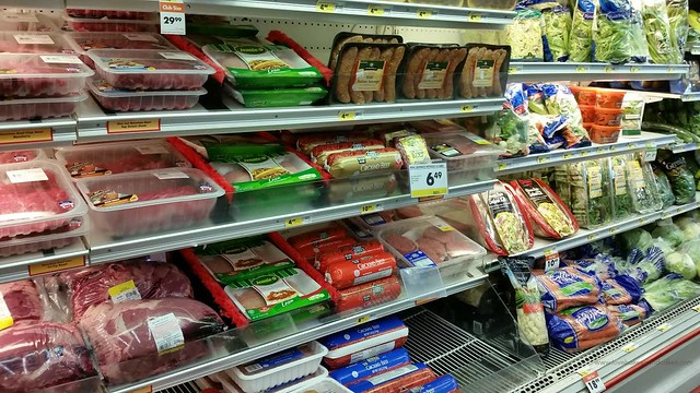 A grocery store cold section with products on the shelf.