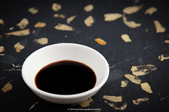 A bowl of soy sauce (also called soya sauce).