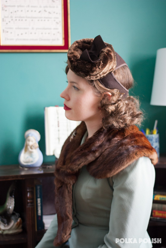 Classic Old Hollywood style with a soft sage green 1940s suit and rich brown fur collar and hat