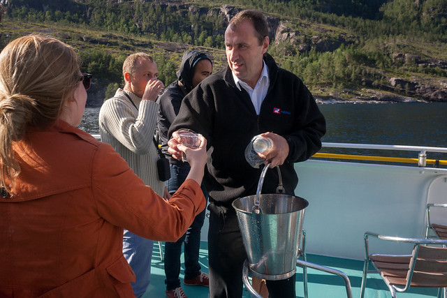 Getting water from the waterfall on the fjords cruise, Bergen