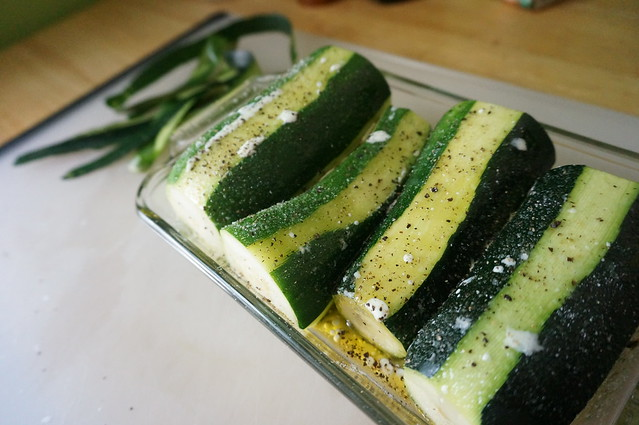 Zucchini ready for their hot oil and cream spa session: droplets of cream and oil stick to the zucchini in their dish, flecked with salt and pepper
