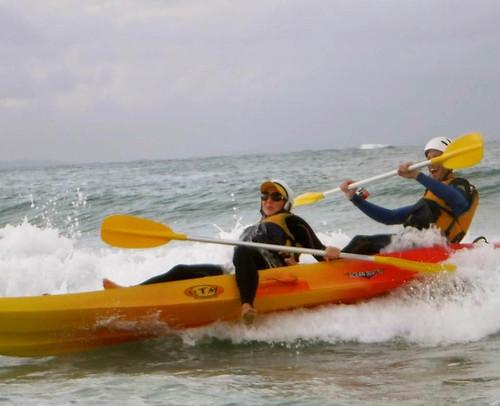 Wellenreiten im Kayak zurückan den Strand.Man beachte die unterschiedlichen Gesichtsausdrücke