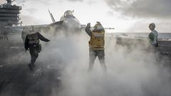 Sailors direct the pilot of an F/A-18E Super Hornet on the flight deck of USS Carl Vinson (CVN 70), Nov. 21. (U.S. Navy/PO2 Sean M. Castellano)