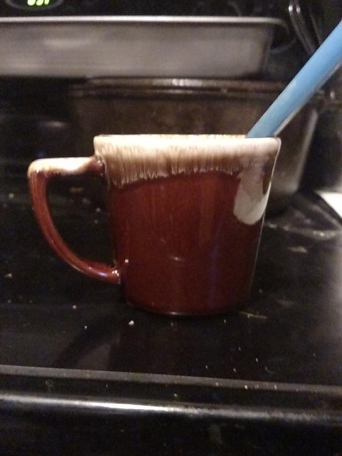 Your average coffee mug. It's a medium dark brown, with cream colored glaze around the rim and at the top of the handle.