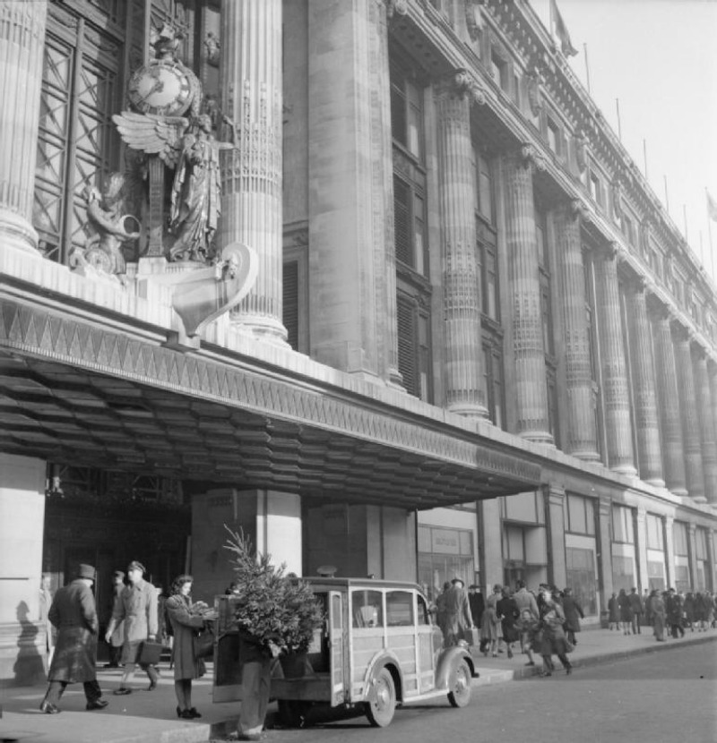 Outside the main entrance to Selfridge's department store on Oxford Street, representatives of the YMCA load the Christmas tree they have just purchased into their van