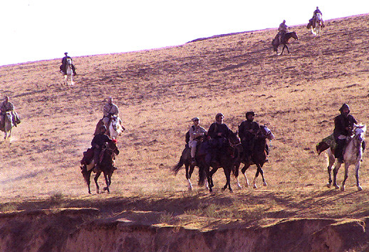 U.S. special forces troops with members of the Northern Alliance ride horseback in Afghanistan