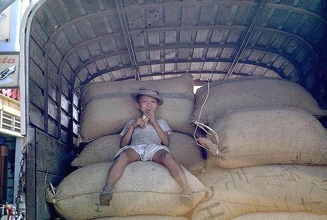 An afternoon in Phan Thiet 1968 - Photos by Ed Blanco - Boy on sacks - Thằng bé trên những bao gạo