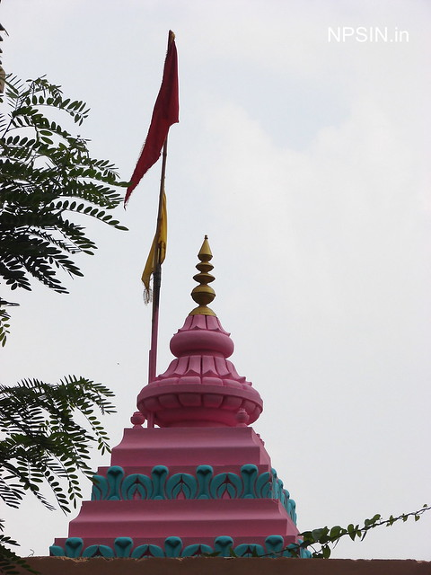 Pink colore shikhar of Shiv Dham with two flags in saffron and yellow color.