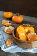 Fresh persimmons and tangerines fruits in bowl