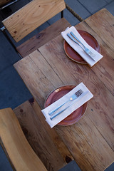 Square wooden table in roped-off area