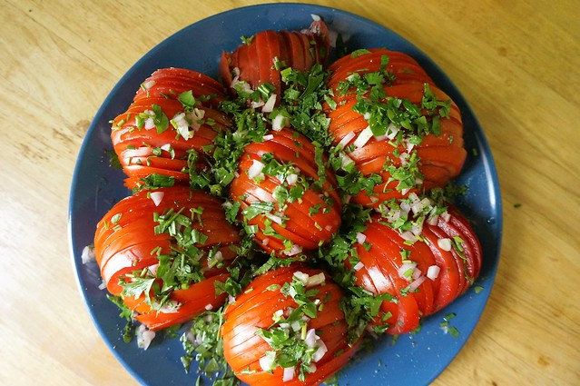 Globes of sliced red tomatoes are arranged on a blue plates, garnished with a scattering of herbs. I *never* do composed salads, but it just feels right in this case.