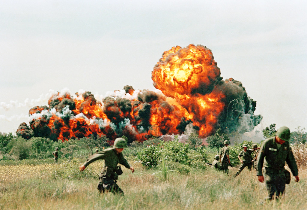 A napalm strike erupts in a fireball near U.S. troops on patrol in South Vietnam , 1966 during the Vietnam War
