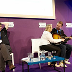 Edwyn Collins & Grace Maxwell with their Chair Ian Rankin | Edwyn's wife Grace strums whilst he plays the chords to A Girl Like You in a special performance at the Book Festival © Helen Jones