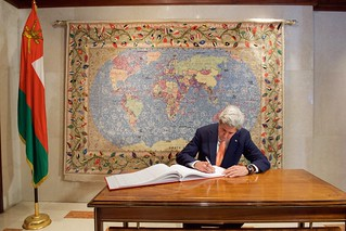 Secretary Kerry, Against the Backdrop of an Omani Rug Depicting a World Map While he Signs the Guestbook