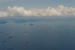 Ships sit an anchor outside the entrance to the Panama Canal as the plane carrying U.S. Secretary of State John Kerry approaches Panama City, Panama, on October 4, 2015, for a refueling stop en route to the 2015 Our Ocean conference in Valparaiso, Chile. [State Department photo/ Public Domain]