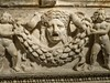 Closeup of tragedic theater mask on a garland sarcophagus with temple roof Roman 150-180 CE