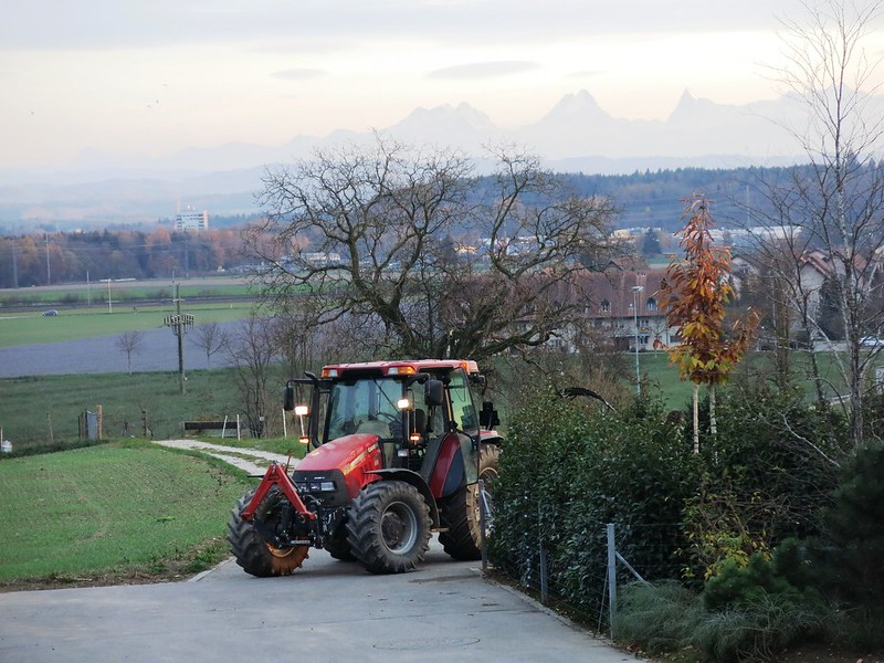 Tractor in Feldbrunnen with alps in background