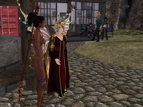 Image Description: Gathering of people near a well. In the foreground, a dark skinned woman wearing mostly fishing nets next to a faerie in formal dress. In the background, an elf and two infernum on the porch of a store.