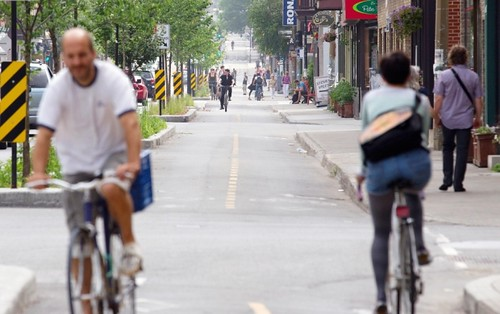 Cyclists ride along the newly widened bike path on Rachel Street, Montreal