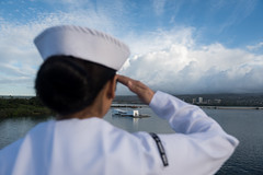 Seaman Eliza Manuel salutes as USS John C. Stennis (CVN 74) passes the USS Arizona Memorial, Dec. 2. (U.S. Navy/PO3 Cole C. Pielop)