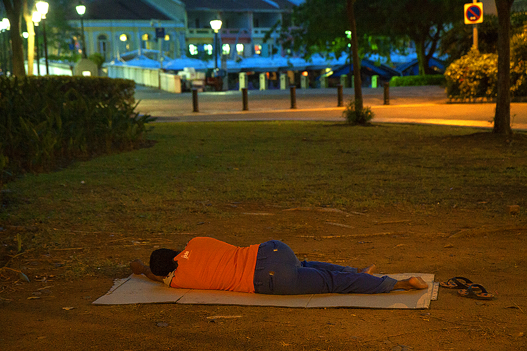 Homeless man sleeping before dawn--Singapore