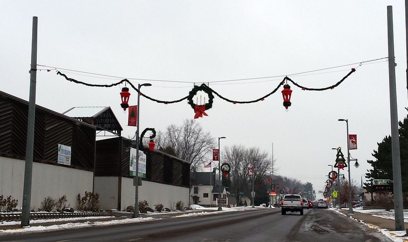 garland with a wreath in the middle and old-style lights on both sides, and tree and wreath decorations on the other light posts down the street