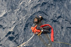 In this file photo, a search and rescue swimmer aboard USS Stethem (DDG 63) retrieves a dummy during a man overboard drill. (U.S. Navy/MC2 Kevin V. Cunningham)