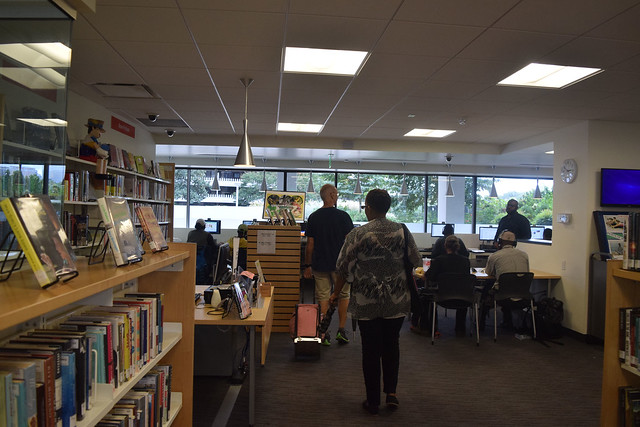 Photo of two people walking past book cases toward several communal tables.