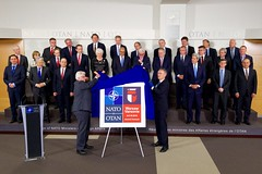 U.S Secretary of State John Kerry and his fellow Foreign Ministers watch as North Atlantic Treaty Organization Secretary General Jens Stoltenberg and Polish Foreign Minister Witold Waszczykowski unveil the logo of next year's NATO Summit Meeting in Warsaw, Poland, during a break at a NATO Ministerial meeting on December 1, 2015, at NATO Headquarters in Brussels, Belgium. [State Department photo/ Public Domain]