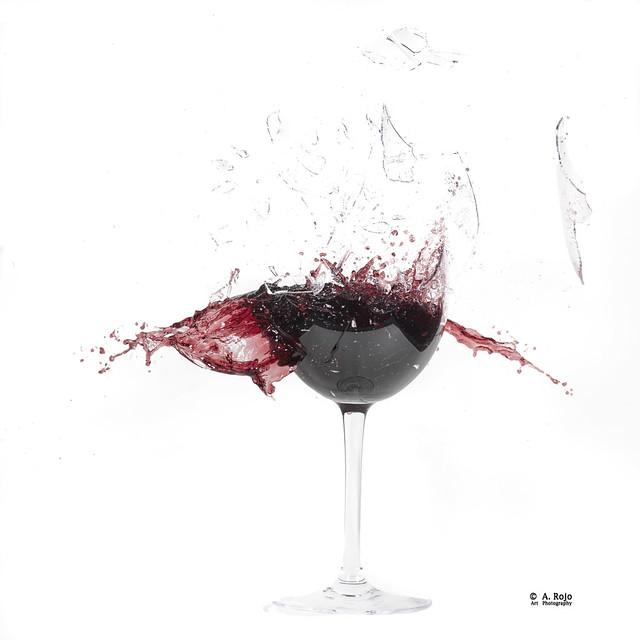Copa de vino tinto recibiendo disparo.