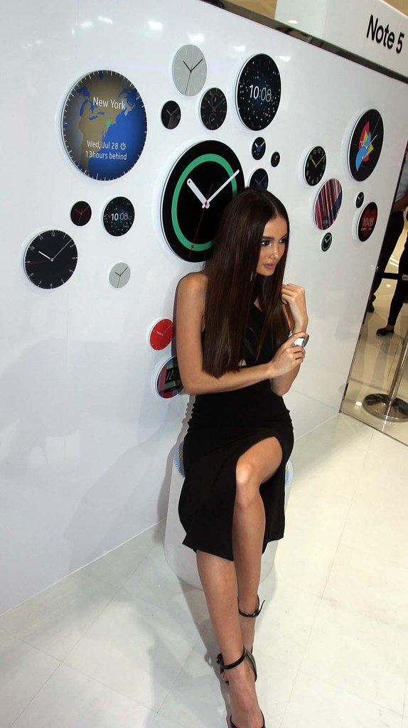 Model Kelsey Merrit strikes a pose in front of a wall displaying the variety of watch faces you can customize the Gear S2