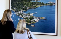 Visitors look at and aerial of American Yacht Club