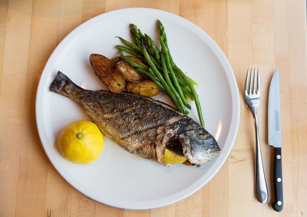 Grilled Branzino fish, stuffed with lemon and thyme, served with roasted potatoes and asparagus