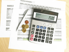 Taschenrechner mit Dokumenten und Geld in Buchhaltung - von oben