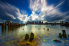 Carlton's Wharf East Boston, Boston Skyline over Boston Harbor through Decayed Pilings with Cloud Movement and Clear Water by Greg DuBois Photography