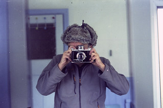 reflected self-portrait with Ensign Selfix 820 camera and trapper hat