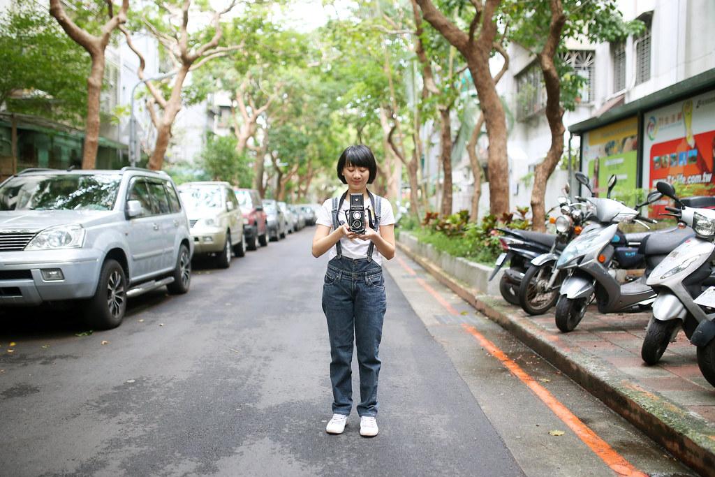 民生工寓 台北 Taipei 2015/11/21 在民生工寓前開始今天的拍攝,我請妹妹拿著 120 的相機,裡面有裝底片,妹妹其實也會攝影,所以就請她真的拍 120 照片,而我從旁邊側拍!  今天早上有下雨,讓柏油路面變得更黑一點。吊帶褲、白色上衣剛好可以對比出妹妹!  Canon 6D Sigma 35mm F1.4 DG HSM Art IMG_9358 Photo by Toomore