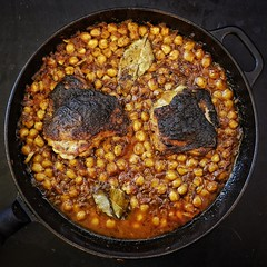 Pan fried chicken and chickpea-harissa on a cast i…