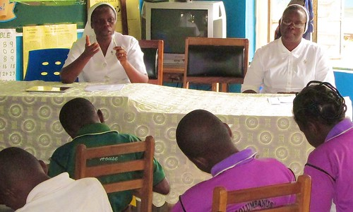 Cecilia lengpang SSL (left) instructing the new school prefects at St Louis Nursery and Primary School, Akure