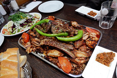 A rectangular metal tray piled with grilled meats including ribs, lamb chops, and chicken wings.  A tomato quarter sits in each corner, and three long green chillies are balanced on top.  Side dishes of bread, salad, and chilli sauce are arranged around it on the table.
