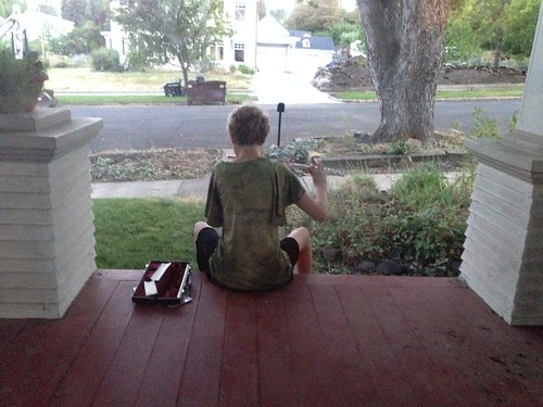 Emma practicing flute on the front porch.